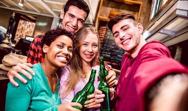Multicultural friends taking selfie and drinking beer at fancy brewery restaurant