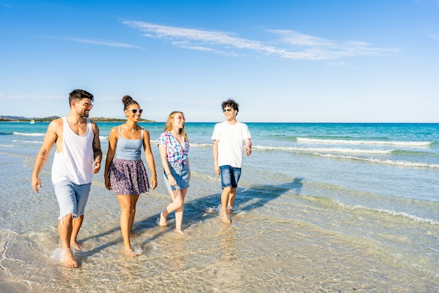 Multicultural friends walking in summer beach vacation in crystal clear water of tropical sea resort