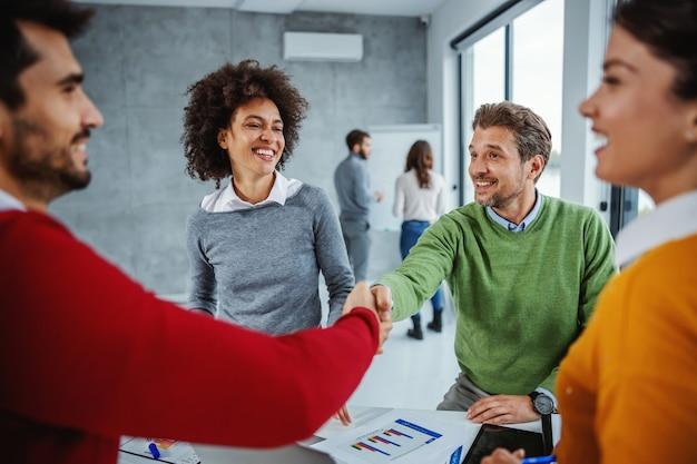 会議室で会議を行うビジネスマンの多文化グループ。彼の新しい若い同僚と握手する成熟したビジネスマン。
