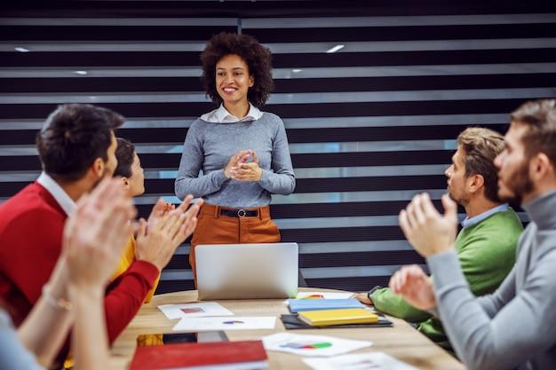 Многокультурная группа деловых людей, встречающихся в зале заседаний. деловая женщина смешанной расы стоя и объясняет идею, пока ее коллеги сидят и хлопают в ладоши.