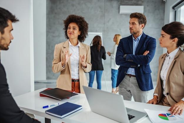 Многокультурная группа деловых людей, стоящих в зале заседаний и имеющих встречу. группа, глядя на бизнесвумен смешанной расы, который объясняет идею.