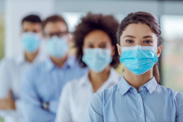 腕を組んでオフィスに立っているフェイスマスクを持つビジネスマンの多文化グループ。フォアグラウンドの女性に選択的に焦点を当てます。