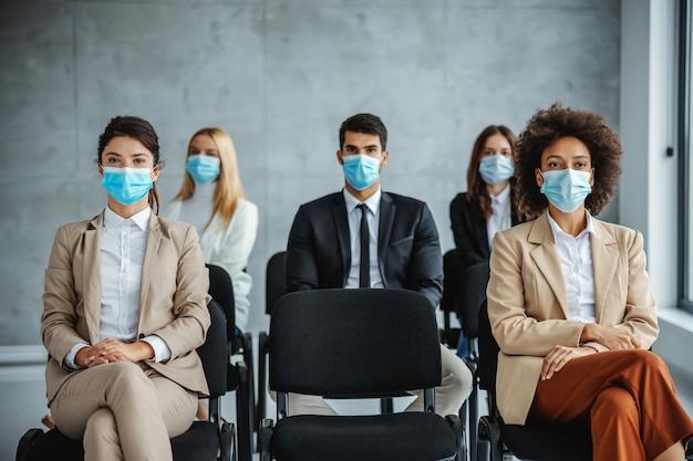 Многокультурная группа деловых людей в масках сидит на семинаре и слушает во время коронавируса.