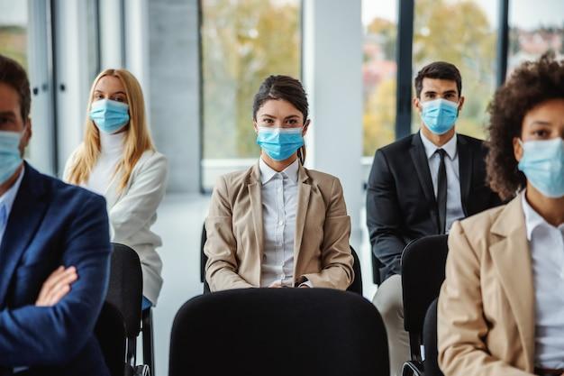코로나 바이러스 동안 세미나에 앉아 얼굴 마스크를 가진 사업 사람들의 다문화 그룹.