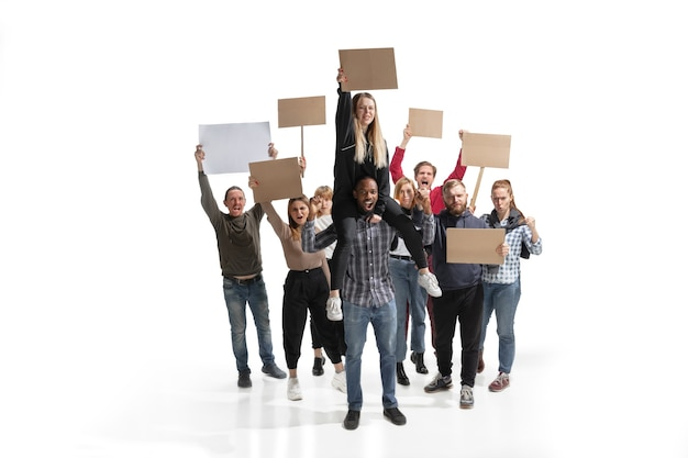 Многокультурная группа людей кричит, держа пустые плакаты на белой стене