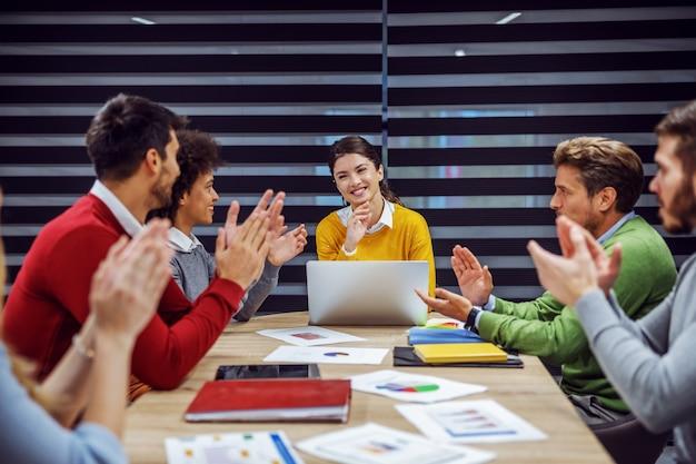 Многокультурная группа позитивных деловых людей, сидящих в зале заседаний на встрече. одна из бизнесвумен сидит и объясняет свою идею, пока ее коллеги хлопают в ладоши.