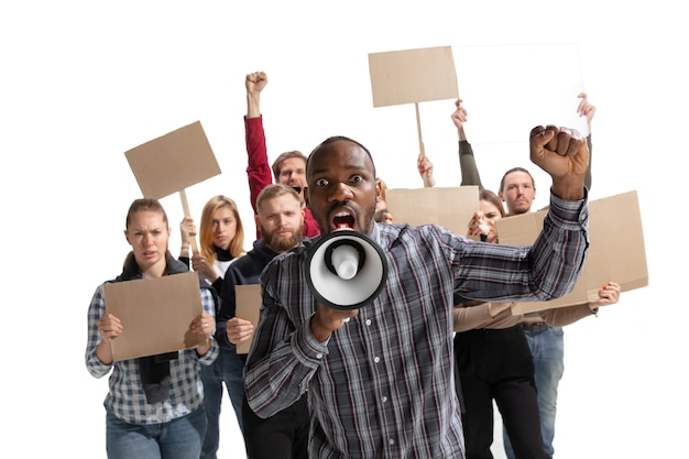 Multicultural group of people screaming while holding blank placards on white wall