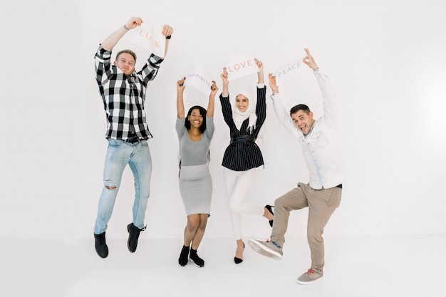 Multicultural group of people standing together over white background and holding up different positive slogans