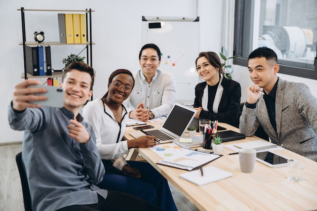 Multicultural group of professional business people making selfie in modern office