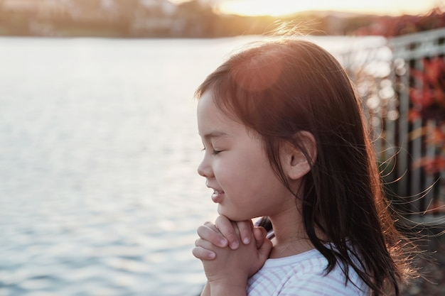 Multicultural little girl praying with sunflare background