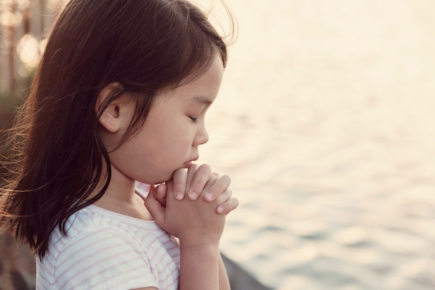 Multicultural little girl praying with sunflare
