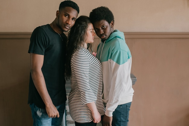 Multicultural love and relationships concept. young white woman standing close between two dark skinned african men. indoor portrait of interracial loving trios. two african guys hugs their girlfrined