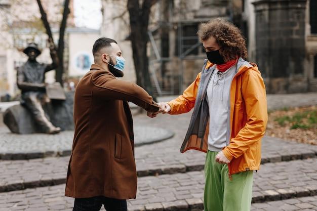 屋外に立っている間拳でぶつかる多文化の男性の友人。医療用マスクを着用し、パンデミック時に距離を保つ2人の男性。