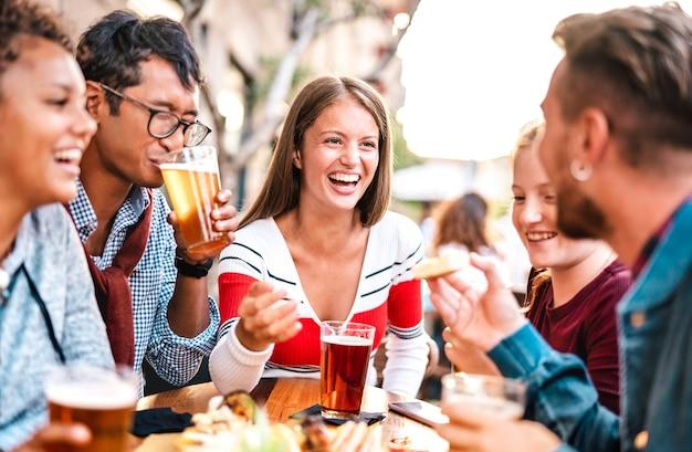 양조장 바 정원에서 맥주를 마시는 다문화 사람들