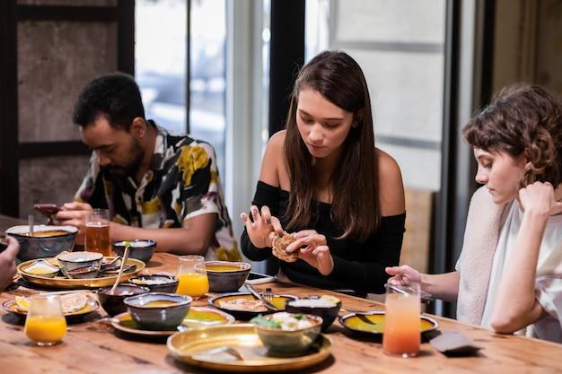 共通キッチンのテーブルに座っている多文化の学生
