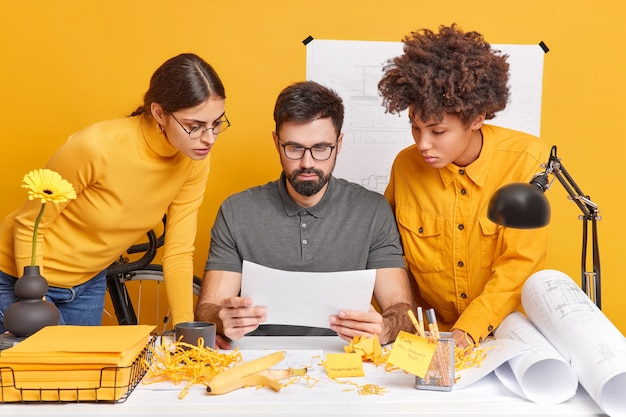 Multicultural team group collaborate together at workplace have brainstroming meeting in office focused attentively at paper try to decide something. man architect with two female assistants