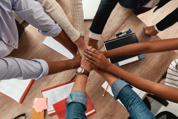 다문화팀. 사무실에 앉아 있는 동안 함께 손을 잡고 있는 사업가들의 최고 전망. 팀워크. 성공