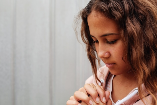 Multicultural teen girl, youth teenager praying with eyes closed