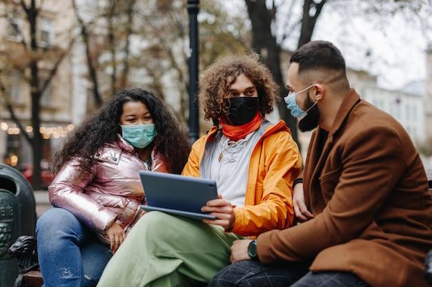 路上で一緒に自由な時間を過ごし、デジタルタブレットを使用している医療マスクの多文化の若者。現代のデバイスで木製のベンチに座っている幸せな男性と女性。
