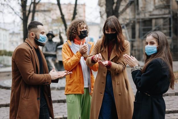 通りに立って、手に消毒剤を適用する医療マスクの多文化の若者。感染症の予防の概念。