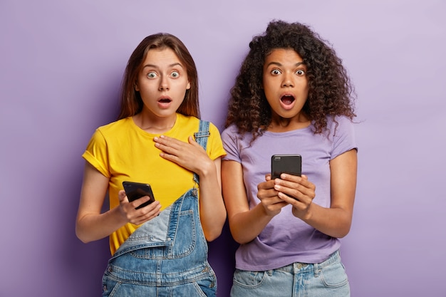 Multiethnic best friend use modern gadgets for watching video in blog, stare with bugged eyes straightly at camera, shocked to have no internet connection