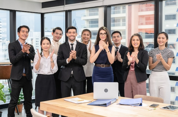 Multiethnic business group clapping hands of successful after business seminar in modern office