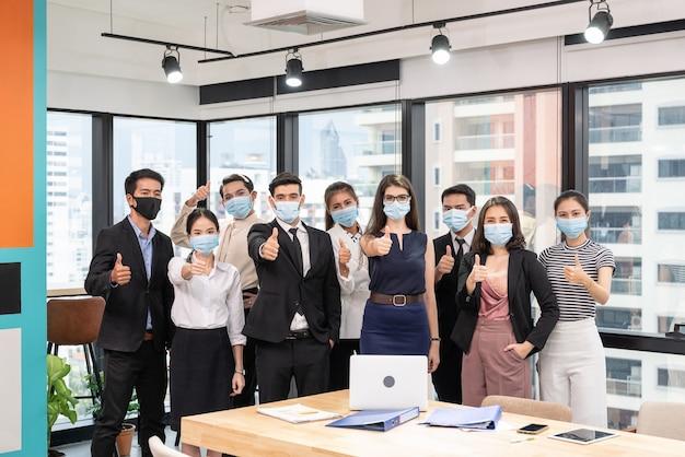 フェイスマスクを着用し、ビジネス地区の新しい通常のオフィスで親指を現して多民族のビジネスグループ