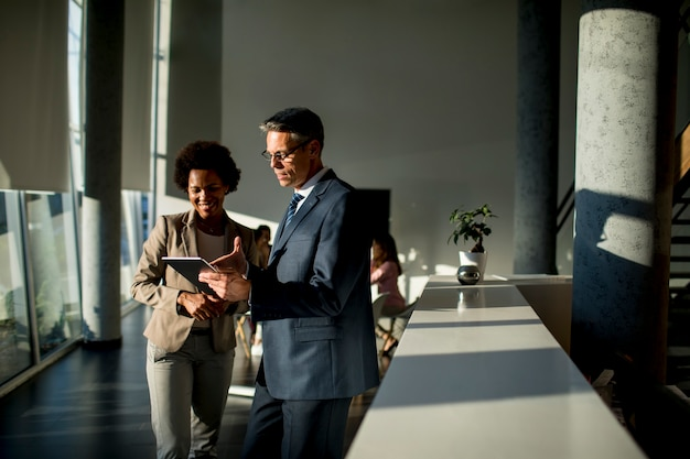 Multiethnic business people using digital tablet while standing in the office