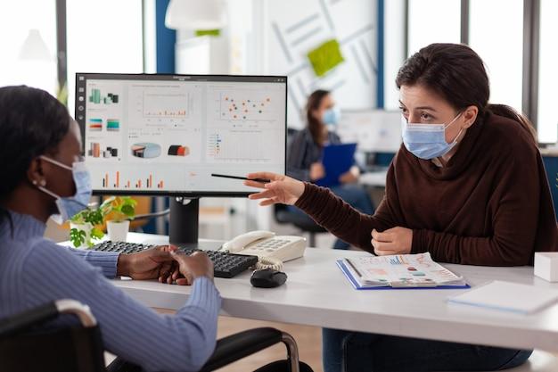 コロナウイルスに対する医療用フェイスマスクを備えた多民族ビジネスチーム