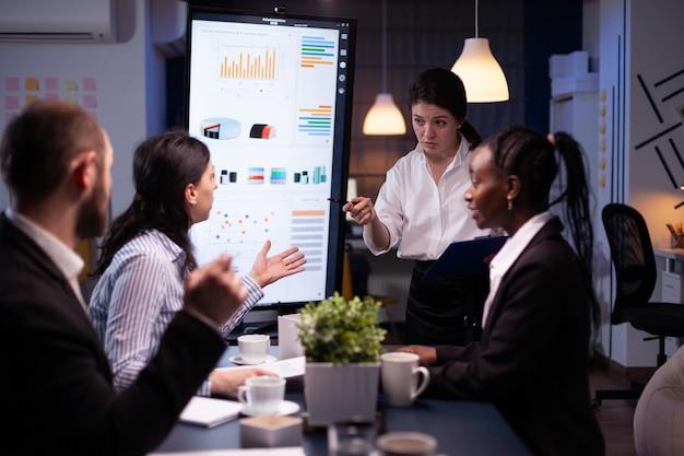Многонациональные бизнесмены обсуждают решение финансовой компании, сидя за столом для переговоров
