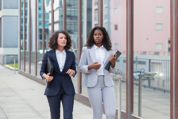 Multiethnic businesswomen with folders on street