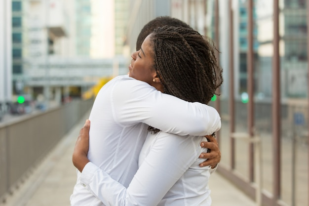Multiethnic close friends wearing white shirts, hugging outside