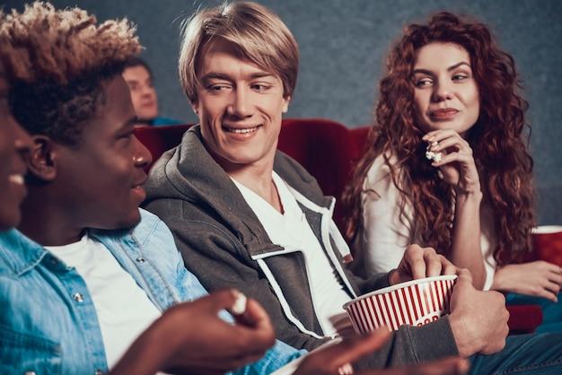 Multiethnic company of friends in cinema