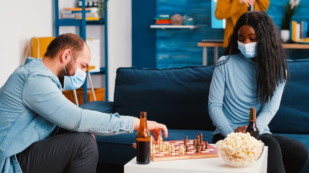 새로운 일반 파티에서 맥주와 간식을 즐기는 보호 마스크를 쓰고 소파에 앉아 체스 게임을하는 다민족 집중된 친구