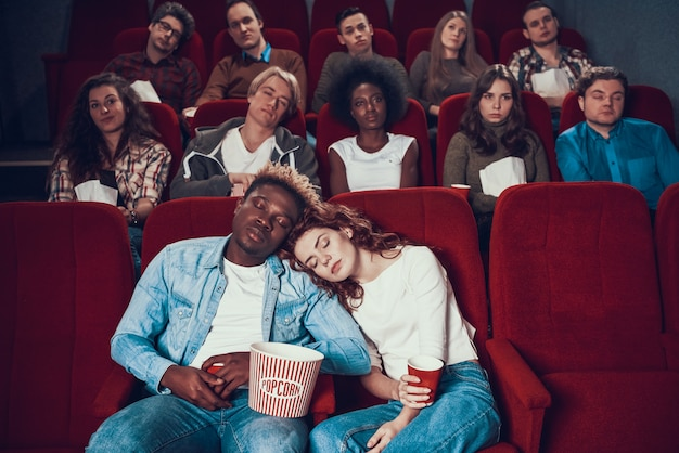 Multiethnic couple in love is sleeping in movie theater