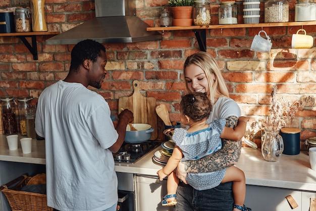 自宅のキッチンで娘と多民族のカップル