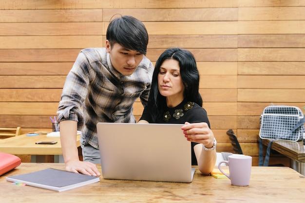 Multiethnic couple working at modern coworking space with a laptop