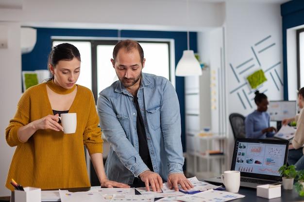 다민족 동료들이 경영진과의 브리핑을 위해 직장 통계 차트에서 논의합니다. 컴퓨터에서 회사 재무 보고서를 분석하는 다양한 기업인 팀. 성공적인 스타트업 기업