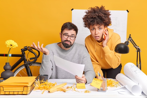 Multiethnic coworkers pose in modern office try to finish designing project. hesitant man holds paper shrugs shoulders with clueless expression. afro american woman tries to help boss talk via phone