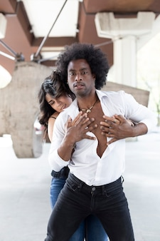 Multiethnic dancers couple passionately holding each others bodies in the street.