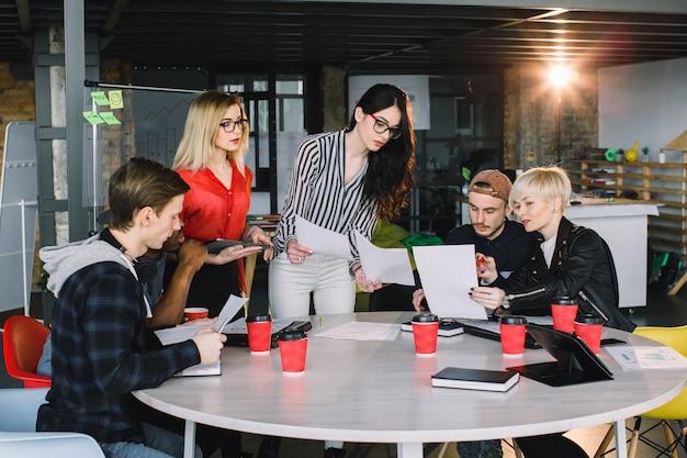 タブレットを使用して、オフィスでの戦略会議またはプロジェクトブレーンストーミングディスカッションのクリエイティブチーム、カジュアルビジネスの人々、または大学生の多民族の多様なグループ。スタートアップまたはチームワークの概念。