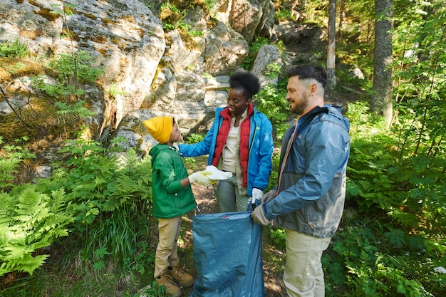 Multiethnic family of three putting garbage into big bags in the forest they save the nature