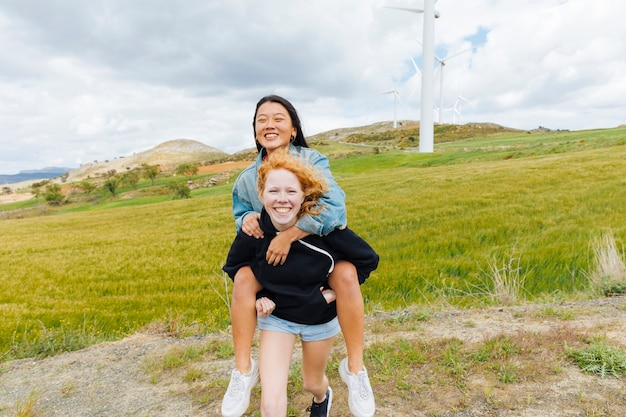 Multiethnic females having fun near wind farm