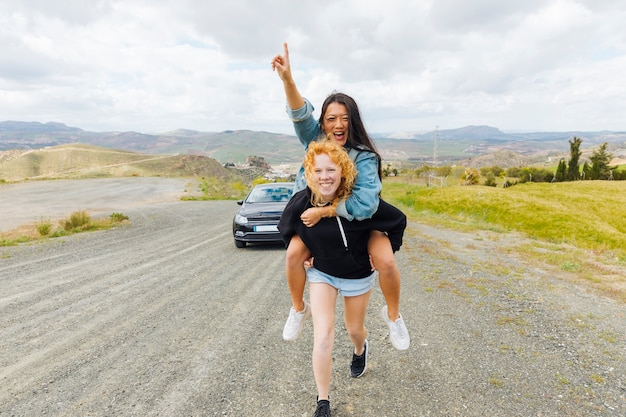 Multiethnic females playing piggyback on roadside