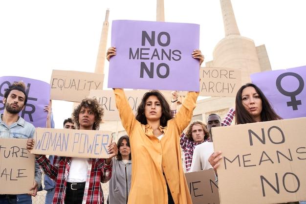 페미니스트 슬로건이 있는 현수막 플래카드를 들고 있는 다민족 페미니스트