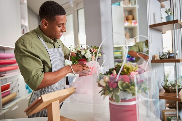 Multiethnic floral designer working at the cash register table and packaging some flowers