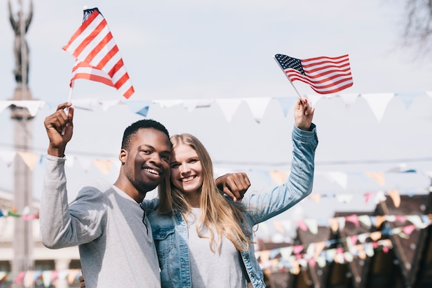 Multiethnic friends holding american flags in outstretched hands