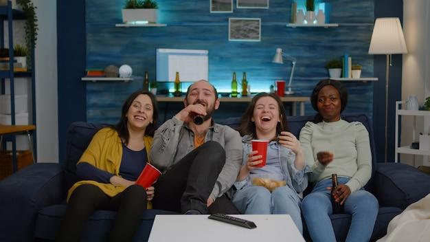 Многонациональные друзья смеются, смотря комедию, наслаждаясь временем, проводят вместе взволнованные смешанные ...