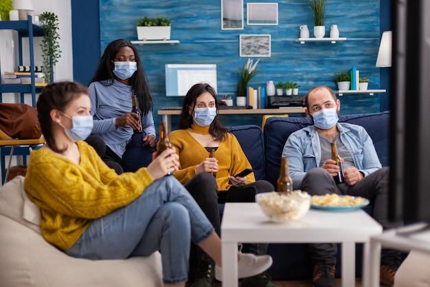 Многонациональные друзья смотрят телевизор, сидя на диване, пьют пиво в маске во время вспышки пандемии covid в качестве профилактики распространения вируса, развлекаясь в свободное время.