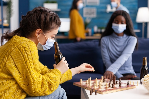 Multiethnic friends playing chess in home living room chatting talking keeping social distancing to prevent illness with covid19 during global pandemic wearing face mask. conceptual image. board games